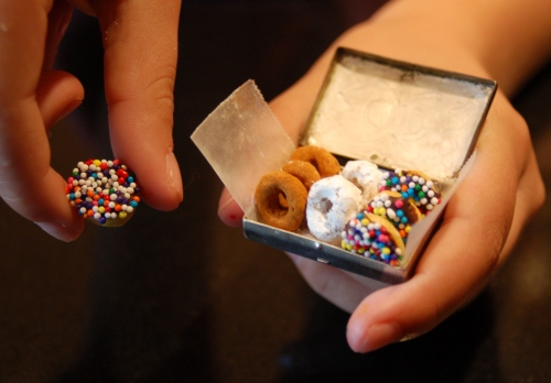 The box of donuts is really a pill box....Emma's holding her favorite, a cheerio dipped in chocolate, then sprinkles. The others are cheerio dipped in confectioners' sugar and cheerios rolled in cinnamon sugar.